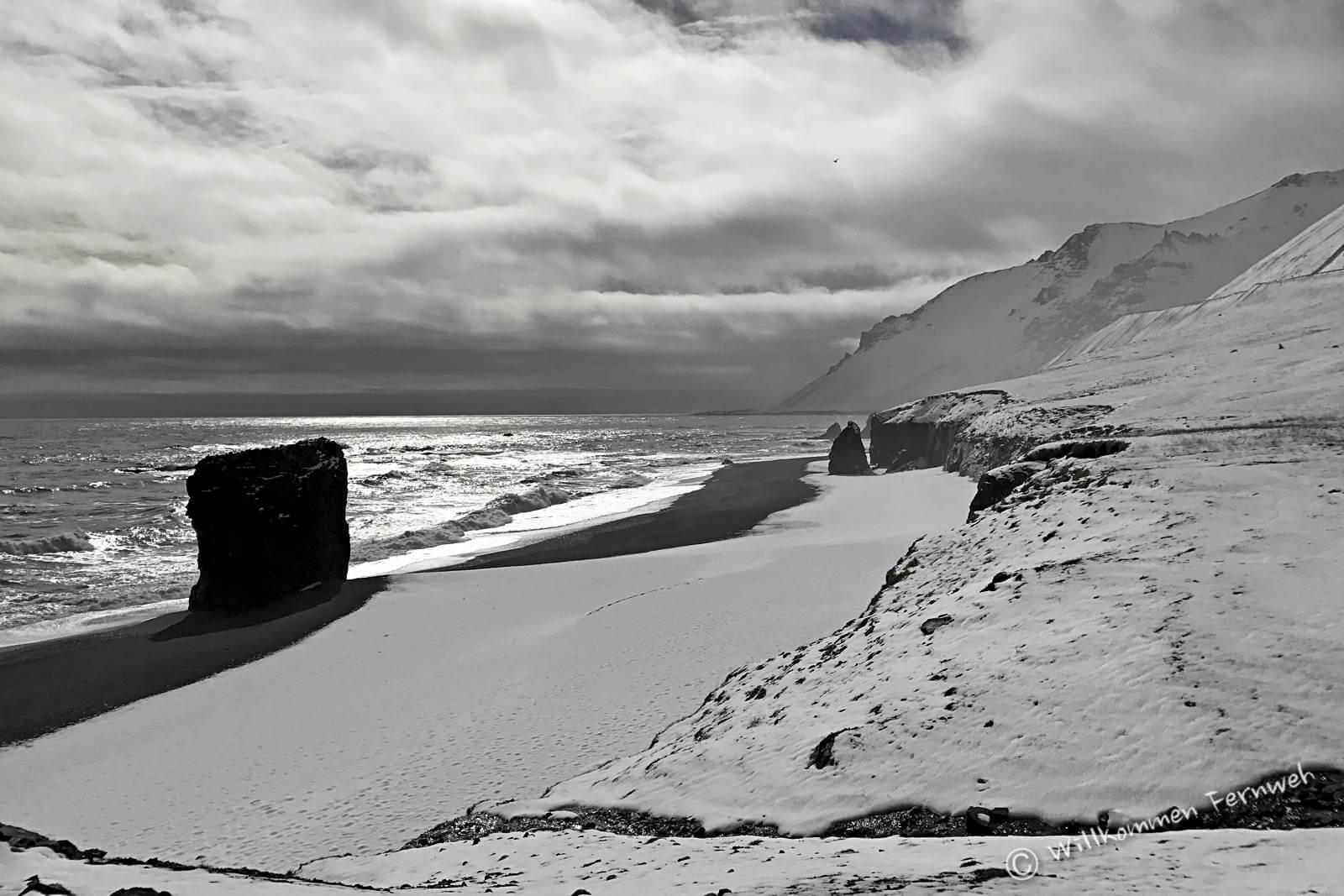 Schwarzer Lavasandstrand und weißer Schnee