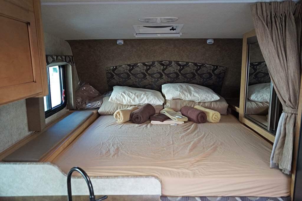 Fraserway Truck Camper von innen: Alkoven mit Bett und Spiegelschrank