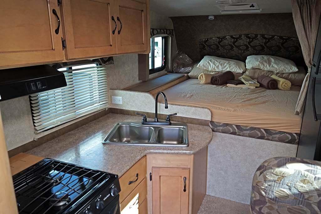 Fraserway Truck Camper von innen: Küche und Alkoven mit Bett